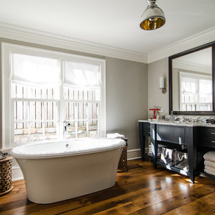 Imagen de cuarto de baño clásico renovado con lavabo encastrado, armarios con paneles lisos, puertas de armario negras, encimera de mármol, bañera exenta y baldosas y/o azulejos beige
