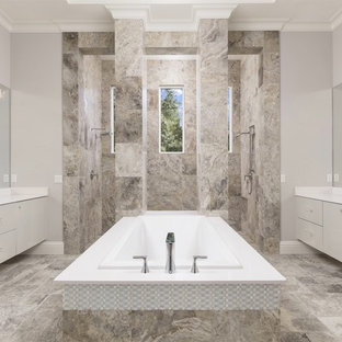 Photo of a mid-sized contemporary master bathroom in Orlando with flat-panel cabinets, a drop-in tub, a double shower, beige walls, an undermount sink, an open shower, grey cabinets, gray tile, travertine, travertine floors and grey floor.