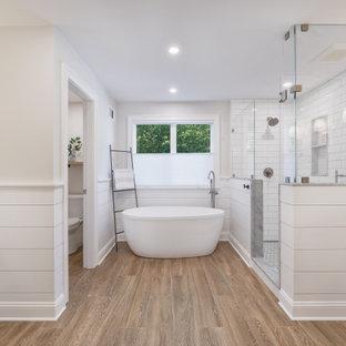 ボストンの広いカントリー風おしゃれなマスターバスルーム (シェーカースタイル扉のキャビネット、白いキャビネット、置き型浴槽、コーナー設置型シャワー、一体型トイレ、白いタイル、サブウェイタイル、グレーの壁、磁器タイルの床、アンダーカウンター洗面器、大理石の洗面台、茶色い床、開き戸のシャワー、マルチカラーの洗面カウンター、トイレ室、洗面台1つ、独立型洗面台、塗装板張りの壁) の写真