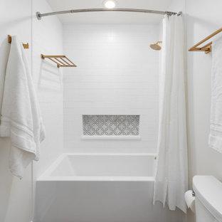 Стильный дизайн: маленькая детская ванная комната в стиле современная классика с фасадами в стиле шейкер, белыми фасадами, ванной в нише, душем над ванной, унитазом-моноблоком, белой плиткой, керамогранитной плиткой, белыми стенами, полом из керамической плитки, врезной раковиной, столешницей из искусственного кварца, коричневым полом, шторкой для ванной, разноцветной столешницей, нишей, тумбой под одну раковину и напольной тумбой - последний тренд