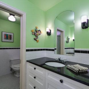Exemple d'une salle de bain chic de taille moyenne pour enfant avec un placard avec porte à panneau encastré, des portes de placard blanches, une baignoire posée, un combiné douche/baignoire, un WC séparé, un carrelage noir et blanc, des carreaux de porcelaine, un mur vert, un sol en carrelage de porcelaine, un lavabo encastré et un plan de toilette en onyx.