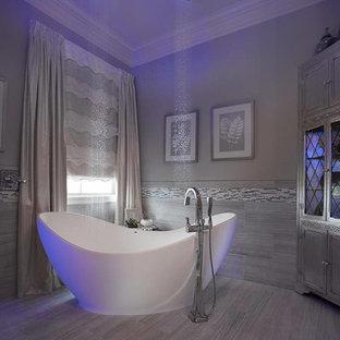 Ejemplo de cuarto de baño principal, clásico renovado, de tamaño medio, con armarios tipo mueble, puertas de armario con efecto envejecido, bañera exenta, ducha abierta, sanitario de dos piezas, baldosas y/o azulejos grises, baldosas y/o azulejos de porcelana, paredes grises, suelo de baldosas de porcelana, lavabo bajoencimera y encimera de granito