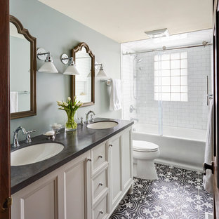 Bild på ett mellanstort vintage badrum, med vita skåp, ett badkar i en alkov, en dusch/badkar-kombination, en toalettstol med separat cisternkåpa, vit kakel, tunnelbanekakel, blå väggar, mosaikgolv, ett undermonterad handfat och bänkskiva i akrylsten