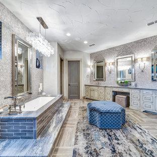 Идея дизайна: главная ванная комната в стиле современная классика с фасадами с утопленной филенкой, искусственно-состаренными фасадами, полновстраиваемой ванной, душевой комнатой, плиткой мозаикой, белыми стенами, полом из плитки под дерево, врезной раковиной, коричневым полом, открытым душем, серой столешницей, унитазом, тумбой под две раковины и встроенной тумбой