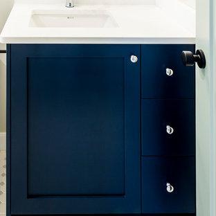 Imagen de cuarto de baño con ducha, contemporáneo, de tamaño medio, con armarios estilo shaker, puertas de armario azules, bañera empotrada, combinación de ducha y bañera, sanitario de una pieza, baldosas y/o azulejos blancos, baldosas y/o azulejos de cemento, paredes blancas, suelo de mármol, lavabo bajoencimera, encimera de acrílico, suelo blanco y encimeras blancas