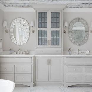 Esempio di una grande stanza da bagno padronale stile marinaro con ante grigie, pareti beige, pavimento in marmo, top in marmo, pavimento grigio, top bianco, ante con riquadro incassato, vasca freestanding, doccia alcova, lavabo sottopiano e porta doccia a battente