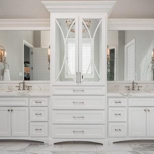 ダラスの広いトラディショナルスタイルのおしゃれなマスターバスルーム (白いキャビネット、白い洗面カウンター、シェーカースタイル扉のキャビネット、グレーの壁、アンダーカウンター洗面器、白い床、置き型浴槽、珪岩の洗面台) の写真
