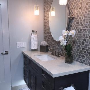 Foto di una stanza da bagno classica di medie dimensioni con lavabo sottopiano, ante in stile shaker, ante in legno bruno, top in quarzo composito, vasca ad alcova, vasca/doccia, piastrelle grigie, piastrelle di ciottoli, pavimento con piastrelle di ciottoli e pareti multicolore