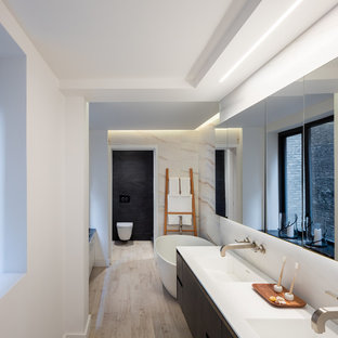 Inspiration for a large contemporary master white tile and marble tile medium tone wood floor and beige floor bathroom remodel in New York with flat-panel cabinets, dark wood cabinets, a wall-mount toilet, black walls, a wall-mount sink, engineered quartz countertops, a hinged shower door and white countertops