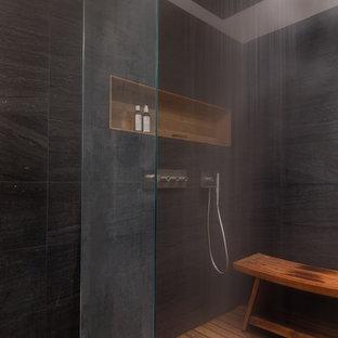 Идея дизайна: большая главная ванная комната в современном стиле с плоскими фасадами, черными фасадами, отдельно стоящей ванной, душем в нише, инсталляцией, черной плиткой, каменной плиткой, черными стенами, светлым паркетным полом, монолитной раковиной, столешницей из искусственного кварца, бежевым полом и душем с распашными дверями