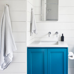 Design ideas for a mid-sized transitional bathroom in Austin with shaker cabinets, blue cabinets, white walls, an undermount sink, black floor and white benchtops.