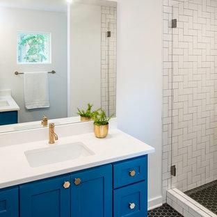 Imagen de cuarto de baño con ducha, clásico renovado, de tamaño medio, con armarios estilo shaker, puertas de armario azules, ducha empotrada, baldosas y/o azulejos blancos, baldosas y/o azulejos de porcelana, paredes blancas, suelo de baldosas de porcelana, lavabo bajoencimera, encimera de acrílico, suelo negro y encimeras blancas