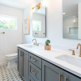 Alcove shower - mid-sized transitional 3/4 cement tile floor and multicolored floor alcove shower idea in Austin with shaker cabinets, gray cabinets, a two-piece toilet, white walls, an undermount sink, white countertops and solid surface countertops