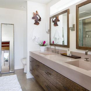 Ispirazione per una grande stanza da bagno padronale minimal con ante lisce, ante con finitura invecchiata, doccia doppia, WC monopezzo, piastrelle grigie, piastrelle in gres porcellanato, pareti bianche, pavimento in gres porcellanato, lavabo integrato e top in cemento