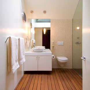 Example of a trendy beige tile and mosaic tile walk-in shower design in DC Metro with a vessel sink, flat-panel cabinets, white cabinets, solid surface countertops and a wall-mount toilet