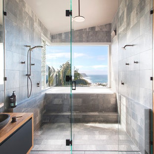 This is an example of a mid-sized beach style master bathroom in Newcastle - Maitland with a drop-in tub, a double shower, gray tile, ceramic tile, grey walls, ceramic floors, wood benchtops, grey floor, flat-panel cabinets, black cabinets, a vessel sink, a hinged shower door and brown benchtops.