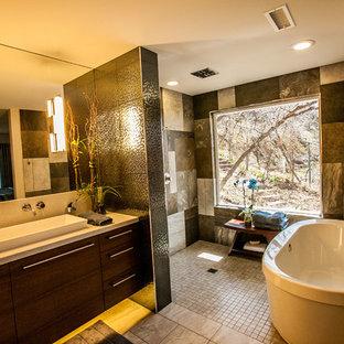 Imagen de cuarto de baño principal, moderno, grande, con armarios con paneles lisos, puertas de armario de madera oscura, ducha abierta, bidé, baldosas y/o azulejos grises, baldosas y/o azulejos de cerámica, paredes beige, suelo de baldosas de porcelana, lavabo de seno grande y encimera de granito