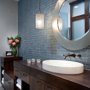 Пример оригинального дизайна: ванная комната в современном стиле с настольной раковиной, плоскими фасадами, темными деревянными фасадами, столешницей из дерева, синей плиткой и удлиненной плиткой