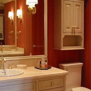 Modelo de cuarto de baño tradicional, grande, con armarios con paneles lisos, puertas de armario blancas, bañera encastrada sin remate, sanitario de una pieza, paredes rojas, suelo de piedra caliza, lavabo encastrado, encimera de piedra caliza y suelo beige