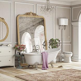 Ispirazione per una stanza da bagno padronale vittoriana con ante in legno chiaro, vasca freestanding, WC a due pezzi, piastrelle in ceramica, pareti beige, parquet chiaro, lavabo sottopiano, top in granito, pavimento marrone e top beige