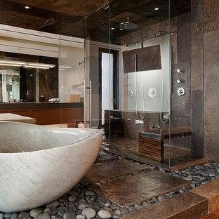 Salle de bain avec un lavabo intégré et un sol en galet ...