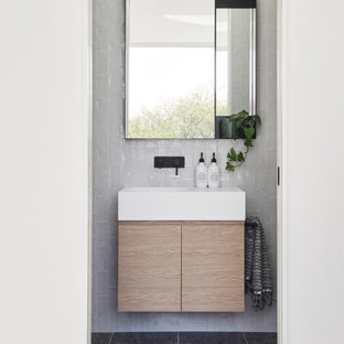 Design ideas for a small contemporary 3/4 bathroom in Melbourne with flat-panel cabinets, beige cabinets, white tile, an integrated sink, grey floor and white benchtops.