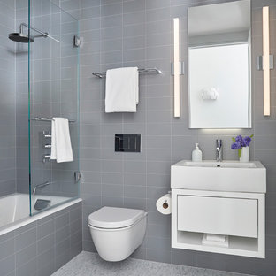 This is an example of a medium sized contemporary ensuite bathroom in New York with flat-panel cabinets, white cabinets, an alcove bath, a shower/bath combination, a wall mounted toilet, grey tiles, porcelain tiles, grey walls, mosaic tile flooring, a vessel sink, grey floors and a hinged door.