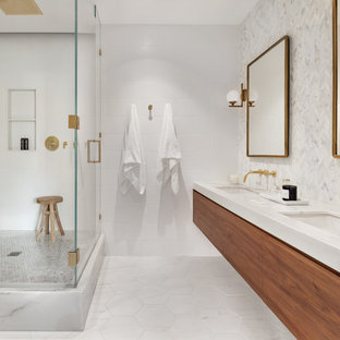 Danish white tile white floor corner shower photo in New York with flat-panel cabinets, medium tone wood cabinets, white walls, an undermount sink, marble countertops, a hinged shower door and white countertops
