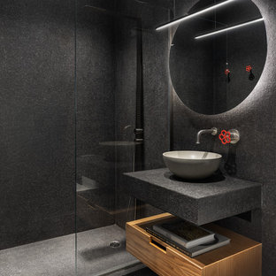 Cette image montre une salle de bain design de taille moyenne avec un placard à porte plane, des portes de placard en bois brun, un carrelage noir, carrelage en mosaïque, un sol en ardoise, une vasque, un sol noir, aucune cabine, un plan de toilette noir, un plan de toilette en carrelage et un mur noir.