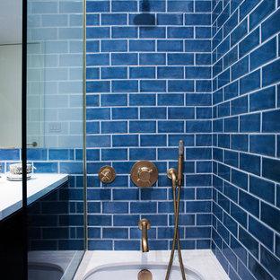 ニューヨークの小さいトランジショナルスタイルのおしゃれなマスターバスルーム (フラットパネル扉のキャビネット、濃色木目調キャビネット、アンダーマウント型浴槽、一体型トイレ、青いタイル、セラミックタイル、白い壁、アンダーカウンター洗面器、珪岩の洗面台) の写真