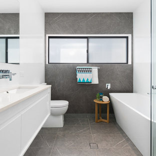 Design ideas for a contemporary bathroom in Sydney with flat-panel cabinets, white cabinets, a freestanding tub, a corner shower, gray tile, white tile, white walls, an undermount sink, grey floor, a hinged shower door and beige benchtops.