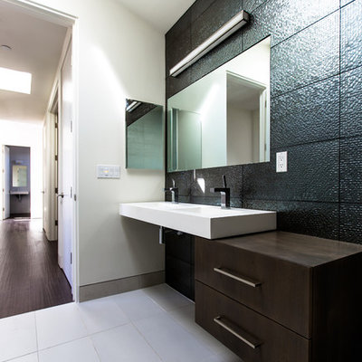 Bathroom - mid-sized modern 3/4 black tile and subway tile ceramic tile and beige floor bathroom idea in San Diego with a vessel sink, flat-panel cabinets, dark wood cabinets, gray walls, solid surface countertops and white countertops