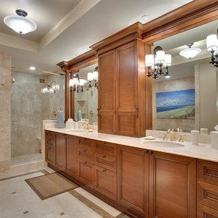 Idée de décoration pour une salle de bain principale ethnique avec un placard avec porte à panneau encastré, des portes de placard en bois brun, une douche d'angle, un carrelage beige, un mur beige et un lavabo encastré.