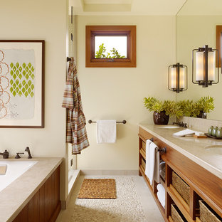 Inspiration for a tropical bathroom in Hawaii with an undermount sink, open cabinets, medium wood cabinets, an undermount tub, an alcove shower, pebble tile floors and beige floor.