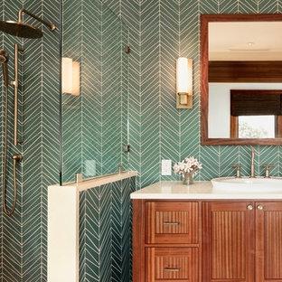 Foto di una stanza da bagno tropicale con ante in stile shaker, ante in legno scuro, doccia ad angolo, piastrelle verdi, pareti verdi, lavabo da incasso e top beige