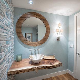 Immagine di una piccola stanza da bagno con doccia tropicale con pareti blu, pavimento in legno massello medio, top in legno, doccia ad angolo, WC monopezzo, lavabo a colonna e pavimento marrone