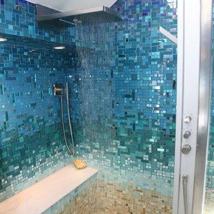 Bild på ett stort tropiskt en-suite badrum, med släta luckor, svarta skåp, ett platsbyggt badkar, en öppen dusch, en toalettstol med hel cisternkåpa, blå kakel, glaskakel, blå väggar, klinkergolv i keramik, ett piedestal handfat, bänkskiva i akrylsten, beiget golv och med dusch som är öppen