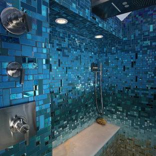 Ispirazione per una grande stanza da bagno padronale tropicale con ante lisce, ante nere, vasca da incasso, doccia aperta, WC monopezzo, piastrelle blu, piastrelle di vetro, pareti blu, pavimento con piastrelle in ceramica, lavabo a colonna, top in superficie solida, pavimento beige e doccia aperta