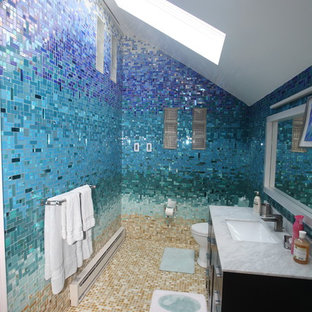 Example of a large island style master blue tile and glass tile ceramic tile and beige floor bathroom design in New York with flat-panel cabinets, black cabinets, a one-piece toilet, blue walls, a pedestal sink and solid surface countertops