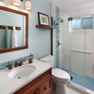Immagine di una piccola stanza da bagno tropicale con lavabo sottopiano, ante con riquadro incassato, ante in legno scuro, top in quarzo composito, doccia alcova, pareti blu e pavimento in gres porcellanato