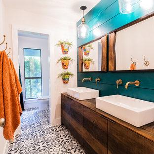 Bild på ett tropiskt brun brunt badrum, med släta luckor, skåp i mellenmörkt trä, blå väggar, mosaikgolv, ett fristående handfat, träbänkskiva och flerfärgat golv