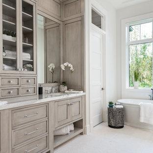 Ispirazione per una stanza da bagno padronale tropicale con ante a filo, ante grigie, vasca freestanding, pareti bianche, lavabo sottopiano, pavimento bianco e top bianco