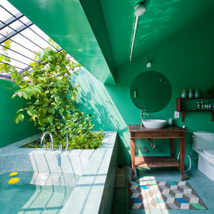 Sauna - tropical concrete floor and blue floor sauna idea in Other with open cabinets, dark wood cabinets, a one-piece toilet, green walls, a vessel sink and wood countertops
