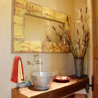 Immagine di una grande stanza da bagno con doccia american style con consolle stile comò, ante marroni, WC a due pezzi, pareti beige, pavimento in pietra calcarea, lavabo a bacinella, top in legno, pavimento beige e top marrone