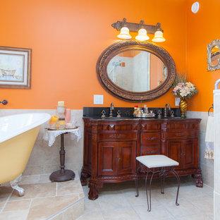 Immagine di una stanza da bagno classica con ante in legno bruno, vasca con piedi a zampa di leone, piastrelle beige, piastrelle in pietra e pareti arancioni