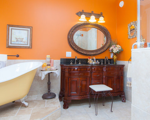 example of a classic clawfoot bathtub design in toronto with dark wood cabinets