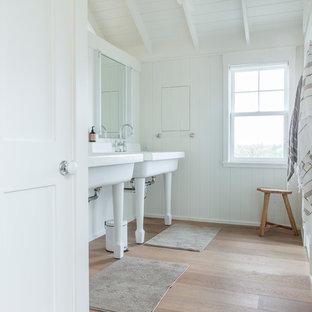 Esempio di una stanza da bagno stile marinaro con lavabo a consolle, pareti bianche, pavimento in legno massello medio e pavimento beige
