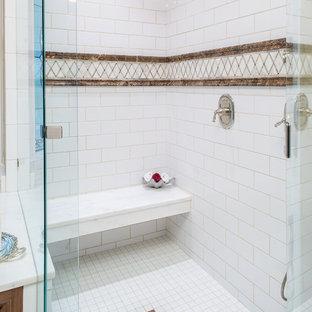 Cette image montre une grand salle de bain principale traditionnelle avec un placard avec porte à panneau surélevé, des portes de placard en bois sombre, une baignoire encastrée, une douche d'angle, un mur beige, un sol en marbre, un lavabo encastré, un plan de toilette en marbre et un banc de douche.
