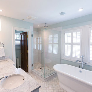 シンシナティの中くらいのトラディショナルスタイルのおしゃれなマスターバスルーム (置き型浴槽、コーナー設置型シャワー、一体型トイレ、グレーのタイル、白いタイル、磁器タイル、青い壁、磁器タイルの床、アンダーカウンター洗面器、ソープストーンの洗面台) の写真