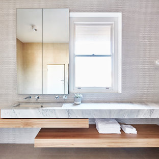 Design ideas for a mid-sized contemporary kids bathroom in Melbourne with flat-panel cabinets, light wood cabinets, white tile, beige walls, porcelain floors, an undermount sink, marble benchtops, beige floor, mosaic tile and white benchtops.